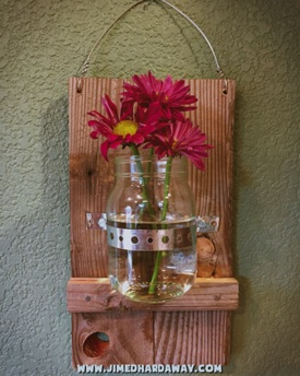 Hanging Flower Jar. This simple and quick build is a great way to liven up a room. A couple of pallet boards, wire, metal strap, and a mason jar. Oh, and some fresh flowers and water of course!